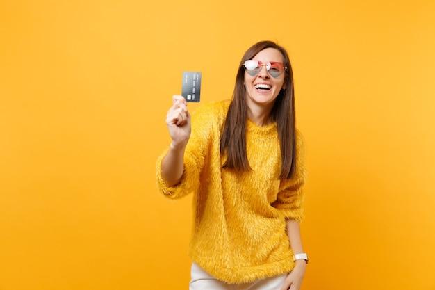 明るい黄色の背景で隔離のカメラでクレジットカードを示す毛皮のセーターとハートの眼鏡で笑っている若い女性の肖像画。人々の誠実な感情、ライフスタイルのコンセプト。広告エリア。