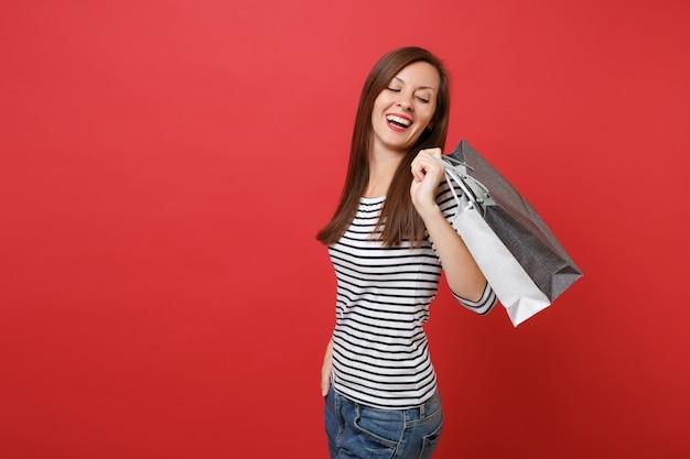 빨간 벽 배경에 격리된 손에 쇼핑을 한 후 구매한 패키지 가방을 뒤돌아보며 웃고 있는 젊은 여성의 초상화. 사람들은 진심 어린 감정, 라이프 스타일 개념입니다. 복사 공간을 비웃습니다.