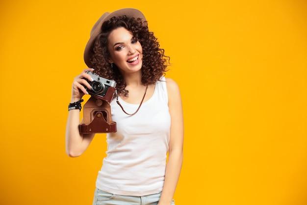 明るい黄色で隔離のレトロなビンテージ写真カメラで写真を撮って笑っている若い女性の肖像画