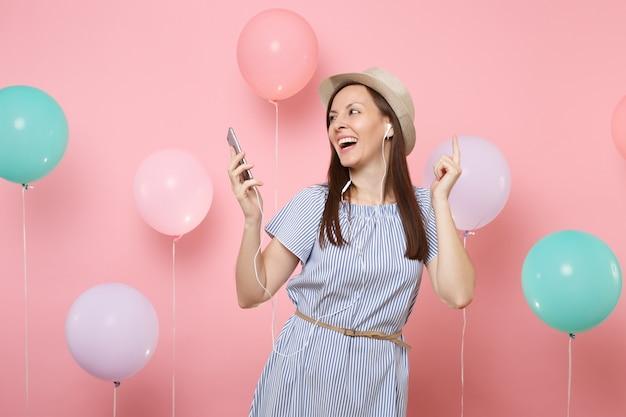 Портрет смеющейся молодой женщины в соломенной летней шляпе и голубом платье с мобильным телефоном и наушниками, слушая музыку на розовом фоне с красочными воздушными шарами. концепция вечеринки по случаю дня рождения.