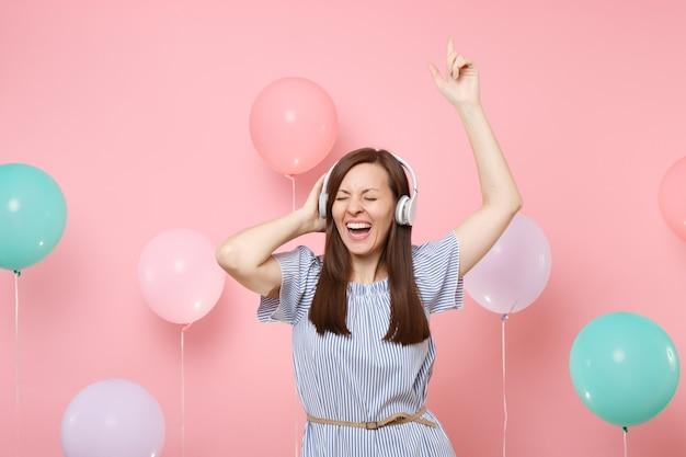Портрет смеющейся молодой женщины с закрытыми глазами в наушниках, носящих голубое платье, слушая музыку, танцы, поднимая руки на розовом фоне с красочным воздушным шаром. концепция вечеринки по случаю дня рождения.