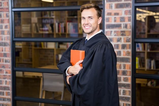 Портрет юриста, стоящего возле библиотеки с книгой по праву в офисе