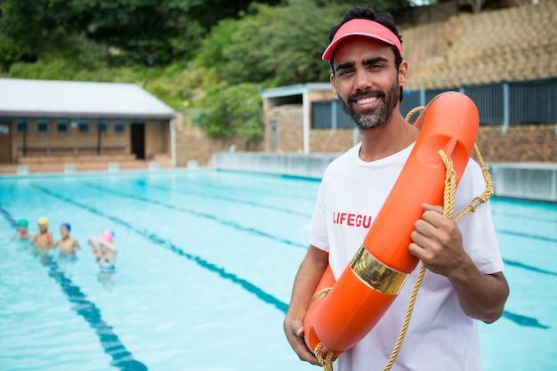 Портрет спасателя, стоящего со спасательным кругом у бассейна