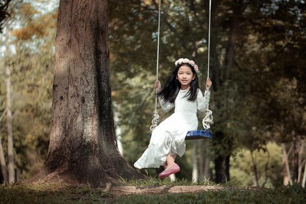 処理されたビンテージトーンと自然の森の大きな木の下でスイングを再生小さなアジアの女の子の肖像画