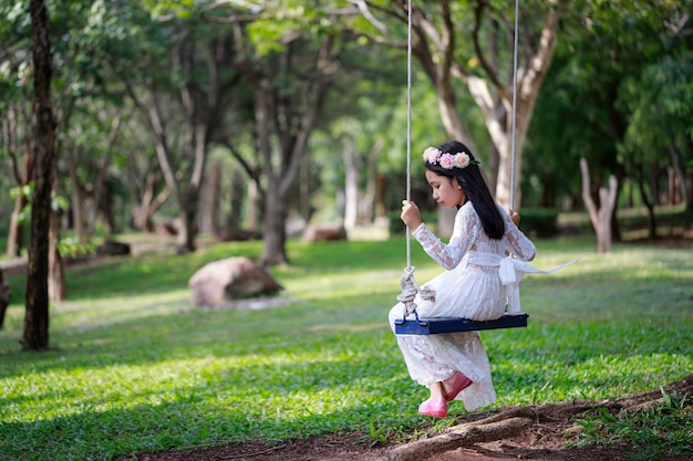 自然の中で大きな木の下でブランコを弾くアジア少女の肖像画