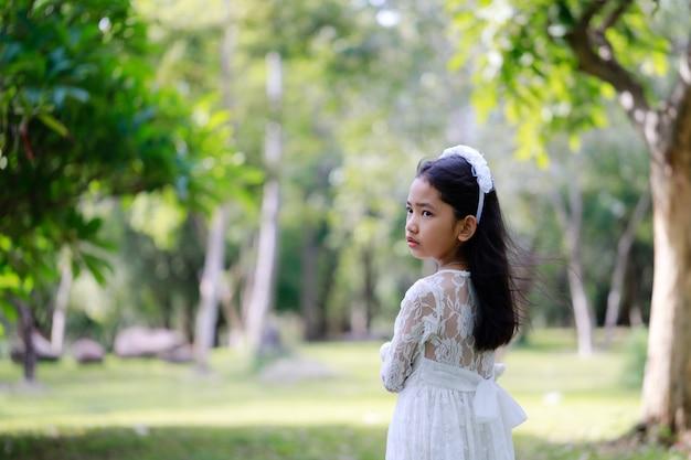 処理された柔らかいトーンの自然林に立っている小さなアジアの女の子の肖像画