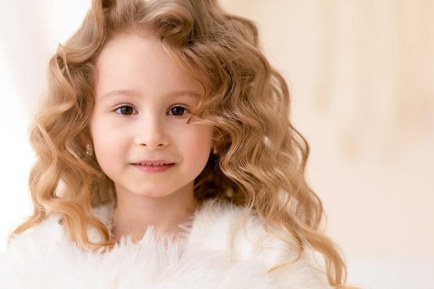 長い巻き毛の白い髪、茶色の目を持つ小さな美しい白人の女の子の肖像画。人間、子供の感情。