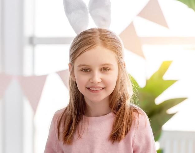 토끼 귀를 착용하고 햇빛이 가득한 방에 머물고있는 작은 아름다운 소녀의 초상화