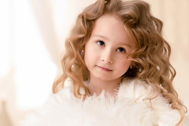 長い巻き毛と茶色の目を持つ小さな美しい少女の肖像画
