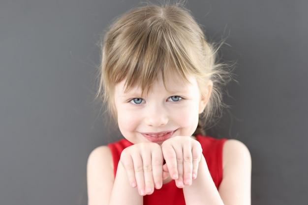 彼女の顔の前に手を持つ小さな美しい笑顔の女の子の肖像画。児童心理学の概念