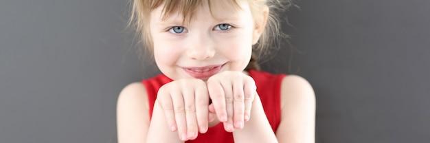 Портрет маленькой красивой улыбающейся девочки с руками перед лицом детской психологии