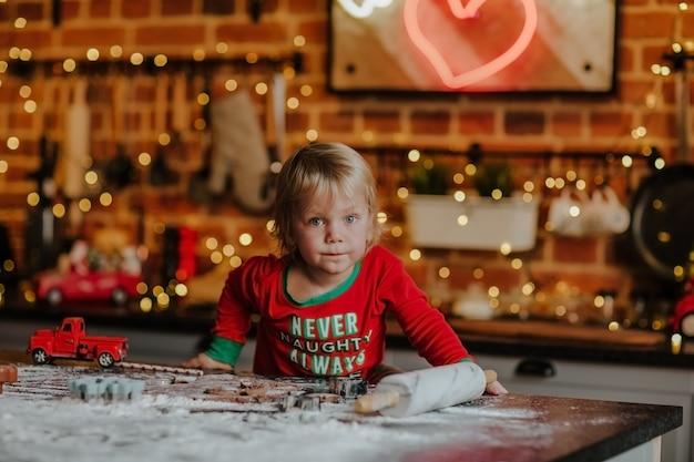 Портрет маленького белокурого мальчика в красной рождественской пижаме, делающей печенье на семейной кухне