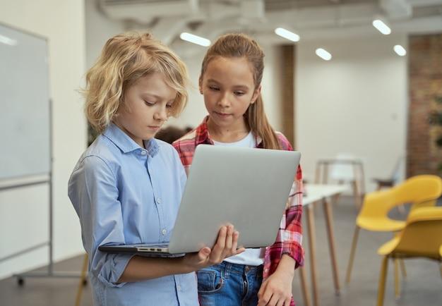 교실에 서 있는 동안 노트북 화면을 들고 보고 있는 어린 소년과 소녀의 초상화