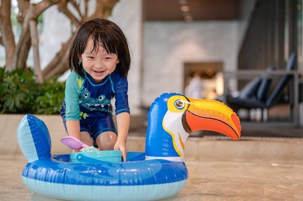 Портрет маленького мальчика в бассейне на смешном надувном поплавке птицы-носорога учится плавать