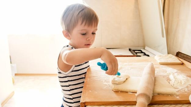 木製のキッチンのカウンターボードで生地を作る小さな男の子の肖像画。 nreakfastのためにパイやクッキーを焼く子供