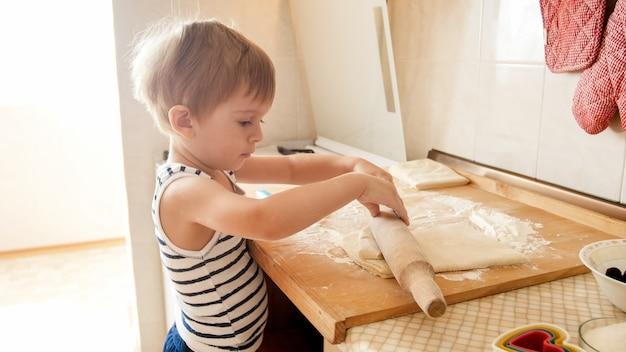 나무 주방 조리대에 반죽을 만드는 어린 소년의 초상화