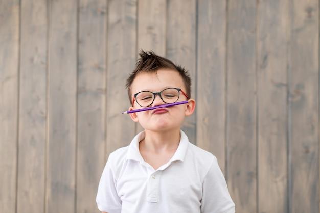 木製の表面で眼鏡と白いtシャツを着ている少年の肖像画
