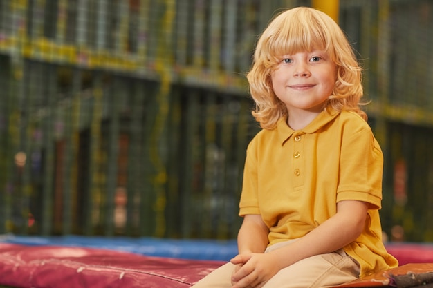 公園でトランポリンに座って正面を見て金髪の少年の肖像画