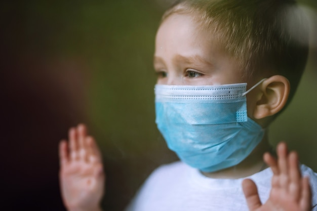 市内のカメラを見ている医療用フェイスマスクを持つ少年の肖像画