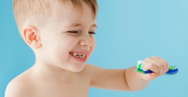 青に歯ブラシを持つ少年の肖像画。