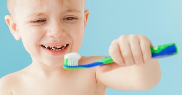 Портрет маленького мальчика с зубной щеткой на синем.