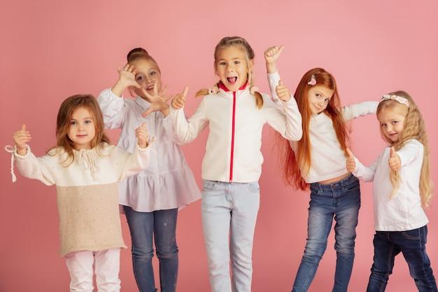 분홍색 스튜디오 배경에 격리된 밝은 감정을 가진 백인 어린 아이들의 초상화