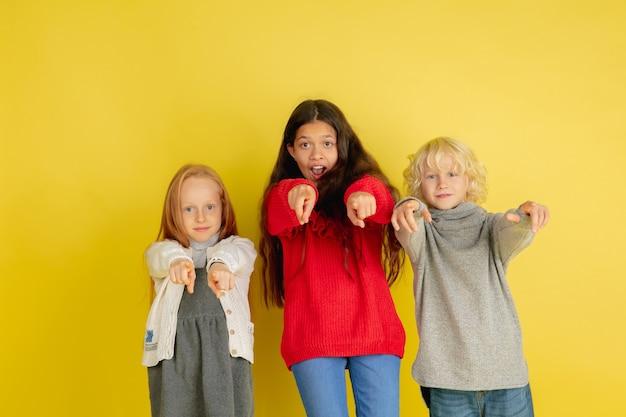 黄色のスタジオの背景に分離された明るい感情を持つ小さな白人の子供たちの肖像画