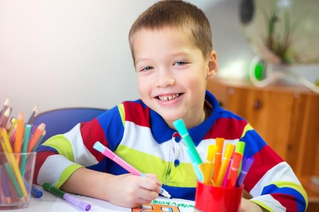 Портрет маленького мальчика, рисующего дом цветными карандашами