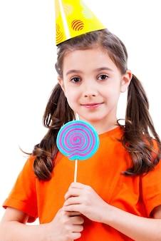 オレンジ色のtシャツと色付きのキャンディーとパーティーハットの小さなかわいい女の子の肖像画-白で隔離