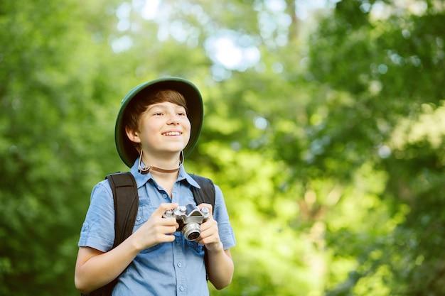 숲에서 사진 카메라로 작은 탐험가의 초상화.