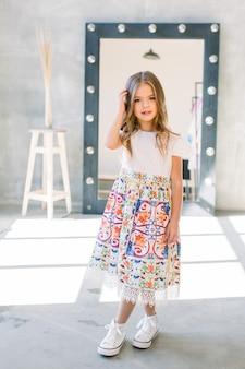 Портрет маленькой модной девочке в белом платье на сером фоне лофта