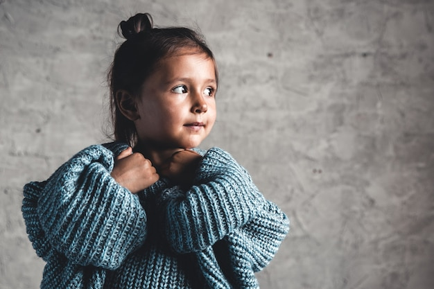 Портрет маленькой девочки ребенка моды на фоне серой стены