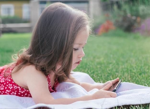 녹색 잔디에 담요에 누워 휴대 전화를 찾고 빨간색에서 어린 소녀 3-4의 초상화. 가제트를 사용하는 어린이