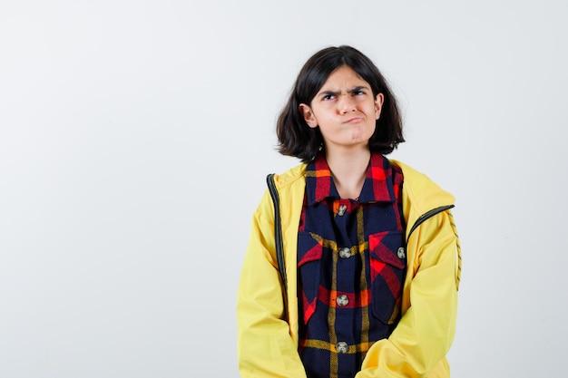 Портрет маленькой девочки, изгибающей губы в клетчатой рубашке, куртке и задумчиво выглядящей, вид спереди