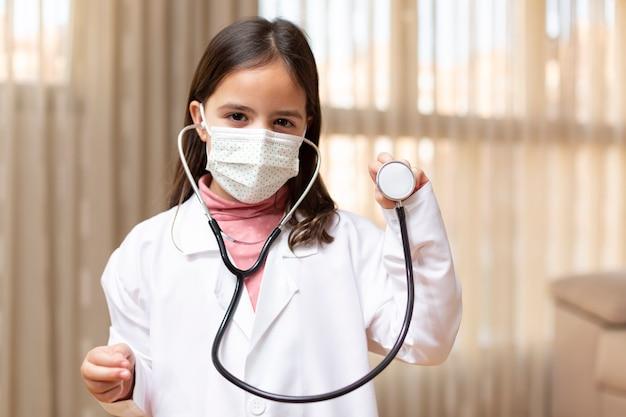 聴診器を使用して医師と医療マスクに扮した少女の肖像画