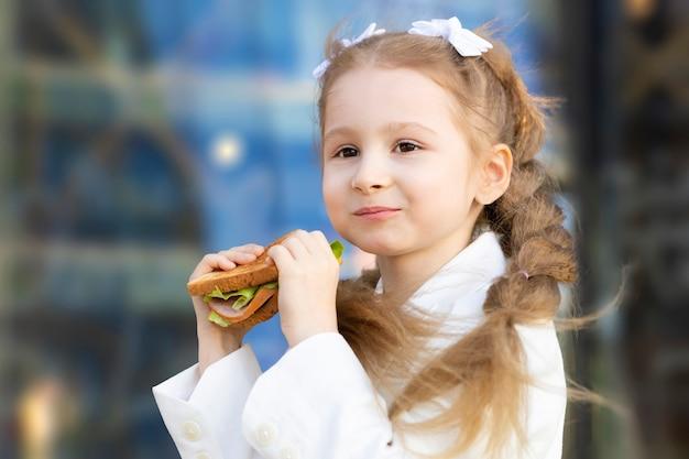 수업 사이 휴식 시간에 샌드위치를 먹는 어린 소녀의 초상화. 아이를 위한 건강에 해로운 음식. 학교에서 아이들을 위한 아침 점심.