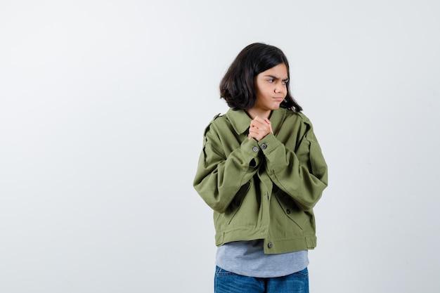 コート、tシャツ、ジーンズで目をそらし、物思いにふける正面図を見ながら握りしめられた手を握っている少女の肖像画