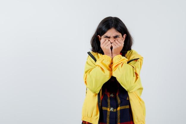 체크 셔츠, 재킷에 입에 손을 잡고 화난 정면을 바라보는 어린 소녀의 초상화