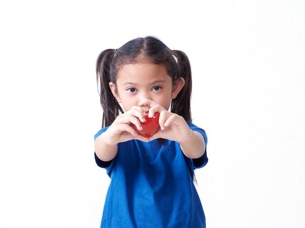 白い背景に赤いハートを保持している少女の肖像画。テキスト用のスペース
