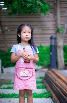 정원에서 박격포와 앞치마에 작은 소녀의 초상
