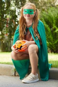 할로윈 파티에 야외에서 앉아있는 동안 호박의 형태로 가방 의상을 입은 어린 소녀의 초상화