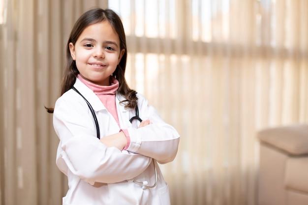 腕を組んで笑顔でポーズをとって医師の制服を着た少女の肖像画
