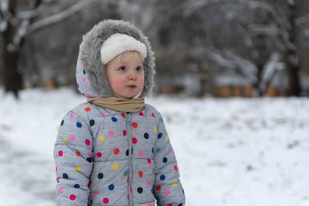 冬の風景を背景にオーバーオールの少女の肖像画。