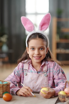 테이블에서 부활절 달걀을 그리는 카메라를 보고 웃고 있는 토끼 귀에 어린 소녀의 초상화