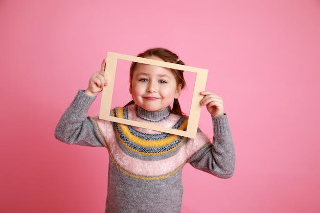 Rosabachgroundのフレームを通して見ている暖かいドレスの少女の肖像画