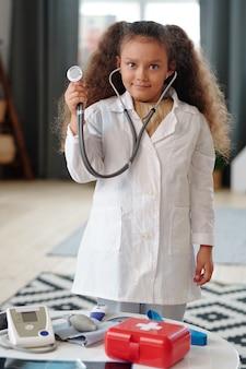 집에서 청진기를 가지고 노는 동안 카메라를 보고 있는 흰색 코트를 입은 어린 소녀의 초상화