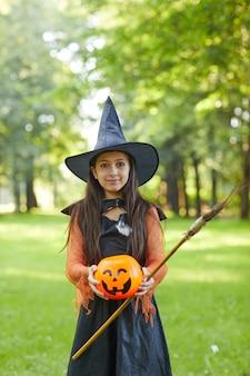 Портрет маленькой девочки в костюме ведьмы, стоя в парке на открытом воздухе