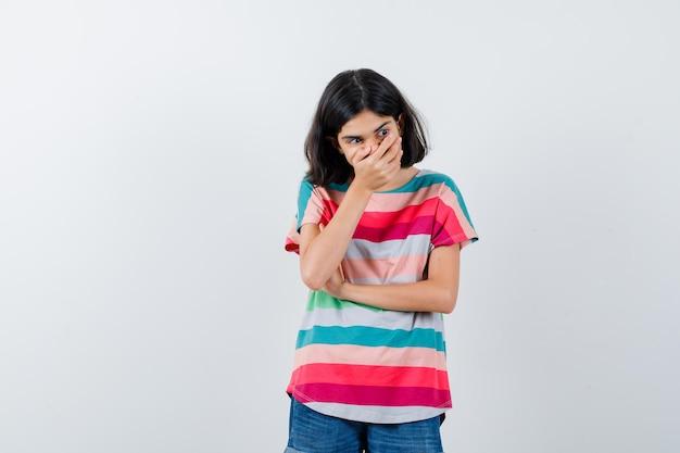 Портрет маленькой девочки, держащей руку во рту в футболке и озабоченной взглядом спереди