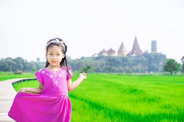 Портрет маленькой девочки на мосту в зеленом поле с храмовым фоном