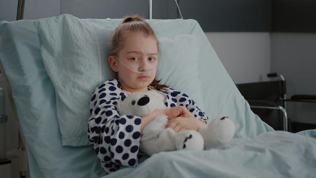 Портрет маленькой девочки-пациента с кислородной носовой трубкой, отдыхающей в постели после перенесенного ...